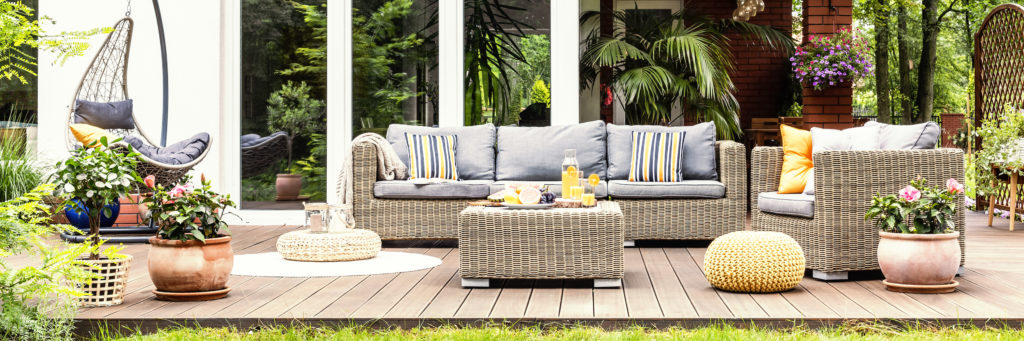 A relaxing spot for a warm, summer day - a stylish, wooden terrace with wicker garden furniture, cushions, plants and flowers